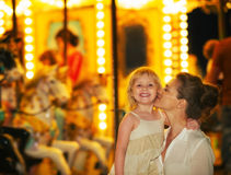Portrait of mother and baby in front of carousel Royalty Free Stock Photography