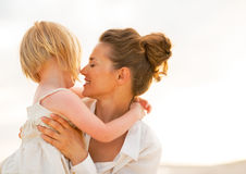 Portrait of mother and baby girl hugging on beach Stock Photo