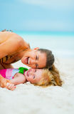 Portrait of mother and baby girl playing on beach. Portrait of happy mother and baby girl playing on beach Royalty Free Stock Photos