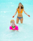 Portrait of mother and baby girl playing in sea royalty free stock image