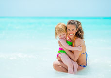 Portrait of mother and baby girl on sea shore Royalty Free Stock Image