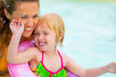 Portrait of mother and baby girl swimming in pool. Portrait of happy mother and baby girl swimming in pool Stock Photos