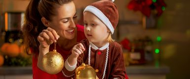Mother and baby holding christmas balls Royalty Free Stock Photography