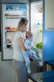 Portrait of mother and baby looking for something to eat in the. Portrait of mother and baby son looking for something to eat in the refrigerator at night Royalty Free Stock Photography