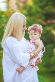 Portrait of mother with baby in summer green park. Outdoors. Stock Image