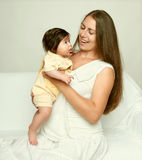 Portrait of mother and baby on white, yellow toned Royalty Free Stock Image
