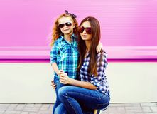 Portrait mother with child girl in checkered shirts, sunglasses in city on colorful pink wall stock photo