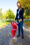Portrait of mother and child. Mom holds baby yellow leaf Royalty Free Stock Image