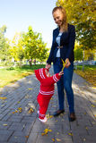 Portrait of mother and child. Mom holds baby yellow leaf Stock Photo