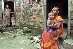 Portrait of mother and child in poverty environment. BANGLADESH, capital, city Dhaka: group, family portrait [full-length, red carpet] of mother with handicapped stock images