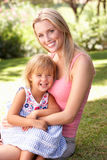 Portrait Of Mother And Child Relaxing In Park Stock Images