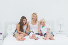 Portrait of mother and children reading a magazine Royalty Free Stock Photo