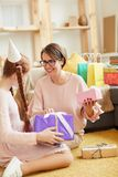 Opening Birthday Gifts. Portrait of mother and daighter opening presents at home Birthday party, copy space stock images