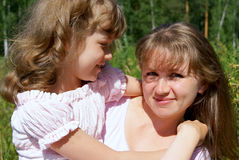 Portrait of mother and daughter. The girl looks at mum and embraces in its summer in park Royalty Free Stock Photo