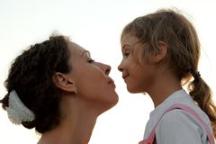 Portrait of mother and daughter. Looking to each other, side view, outdoor Stock Photo