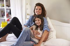 Portrait Of Mother And Daughter On Bed Using Digital Tablet Stock Photos