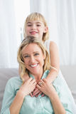 Portrait of a mother and daughter behind her on the couch Royalty Free Stock Photography