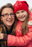 Portrait of mother and daughter embracing smiling at camera outdoors Stock Photos