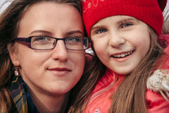 Portrait of mother and daughter embracing smiling at camera outdoors Royalty Free Stock Image