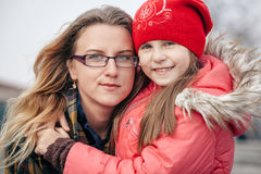 Portrait of mother and daughter embracing smiling at camera outdoors Stock Images