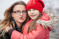 Portrait of mother and daughter embracing smiling at camera outdoors Stock Image