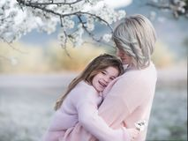 Portrait of mother and daughter gently embrace in the garden with flowering almendra. Family love and lifestyle. Portrait of mother and daughter gently embrace Royalty Free Stock Photo
