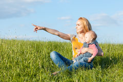 Portrait of mother and daughter in the grass. Mom points hand forward Royalty Free Stock Images