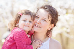 Portrait of mother and daughter kissing laughing Stock Image