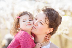 Portrait of mother and daughter kissing laughing stock photo
