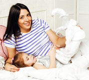 Portrait of mother and daughter laying in bed hugging and smilin Stock Photos