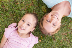 Portrait of mother and daughter lying on grass at park Royalty Free Stock Images