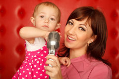 Portrait of mother and daughter with microphone Stock Image