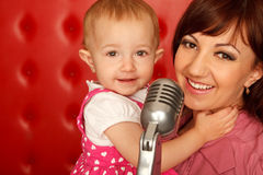 Portrait of mother and daughter with microphone Stock Photo