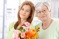 Portrait of mother and daughter at Mother's day. Portrait of senior mother and daughter at Mother's day, having flowers, smiling Stock Photo