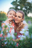 Portrait of mother and daughter on nature in flowers. Royalty Free Stock Photography