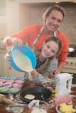 Mother and daughter preparing cup cake in kitchen Stock Images