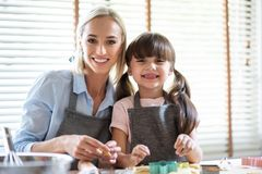 Portrait of Mother and daughter preparing the dough. Portrait of Mother and daughter having fun with preparing the dough, bake cookies in the kitchen. Looking at royalty free stock photos