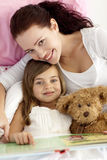 Portrait of mother and daughter reading in bed. Portrait of mother and daughter reading a book together in bed Stock Images