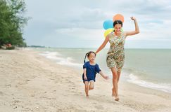 Portrait of Mother and daughter running on beach with colorful balloons in mother hand royalty free stock photo