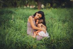 Portrait of a mother daughter. Sensual portrait of a mother daughter sitting on the grass Royalty Free Stock Images