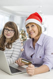 Portrait of mother and daughter shopping online during Christmas Stock Photos