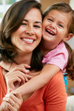 Portrait Of Mother And Daughter Sitting On Sofa At Home Royalty Free Stock Image