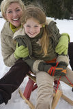 Portrait of mother and daughter on snow sled Royalty Free Stock Image