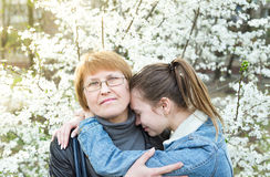 Portrait of mother and daughter. Daughter tenderly embraces mother in the orchard Royalty Free Stock Photos