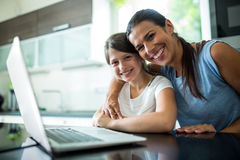Portrait of mother and daughter using laptop and digital tablet in the living room Royalty Free Stock Images
