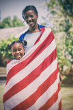 Portrait of mother and daughter wrapped in American flag at park Royalty Free Stock Image