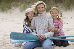 Portrait of mother and daughters on beach with oars Royalty Free Stock Image