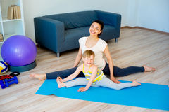Mother doing yoga with daughter Royalty Free Stock Photos