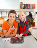 Portrait of mother and girl with baked Halloween biscuits Stock Images