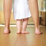 Portrait of a mother helping baby to walk indoors Stock Photos